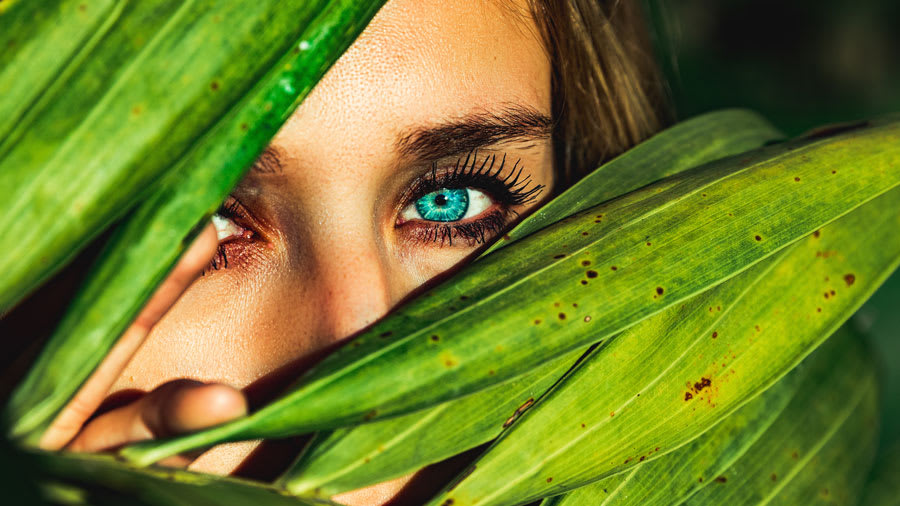 Woman with blue eye visible from behind green leaves