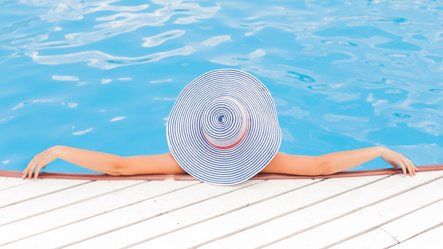 Woman with large brim hat sitting at the edge of the pool