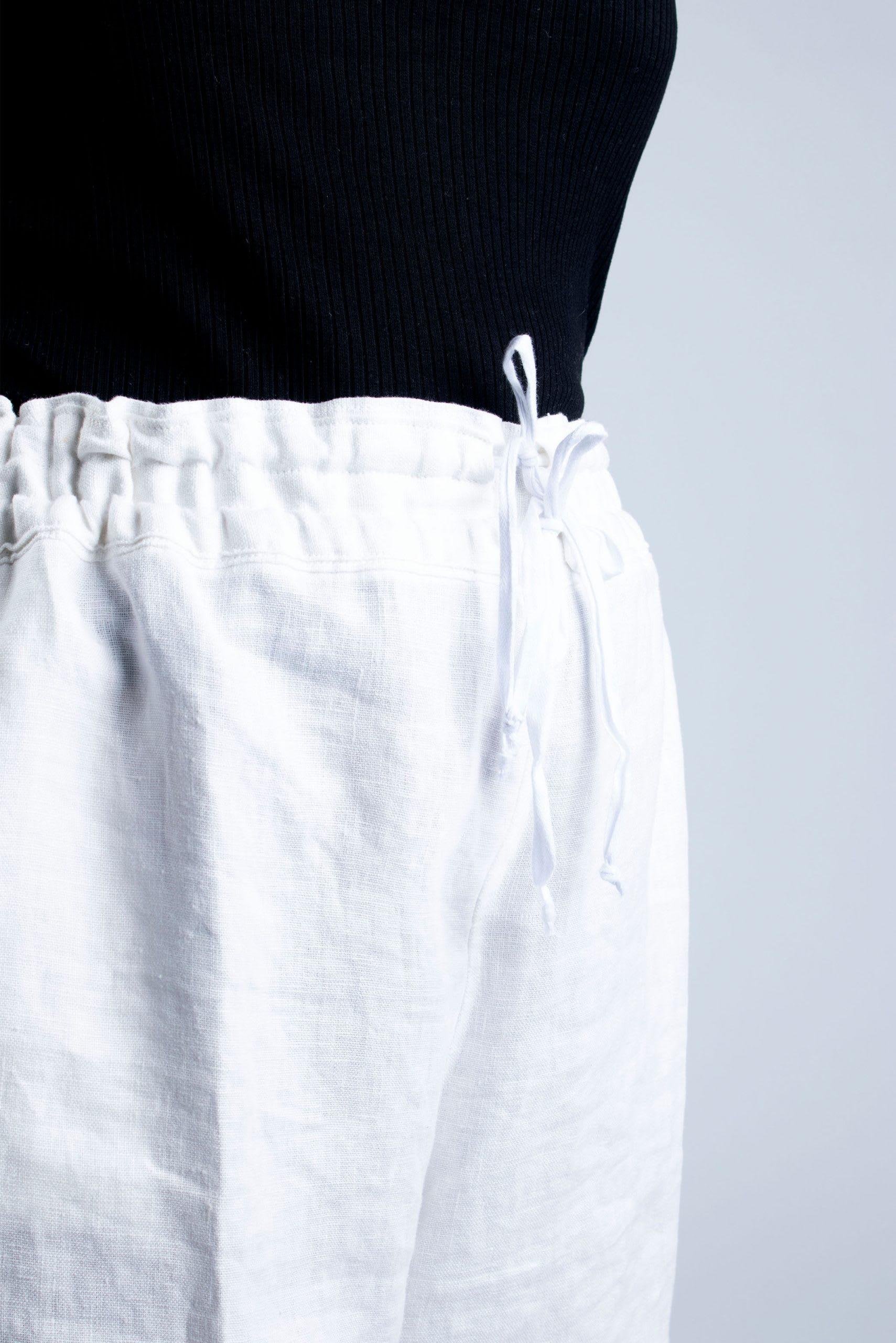 detail of drawstring on white linen shorts
