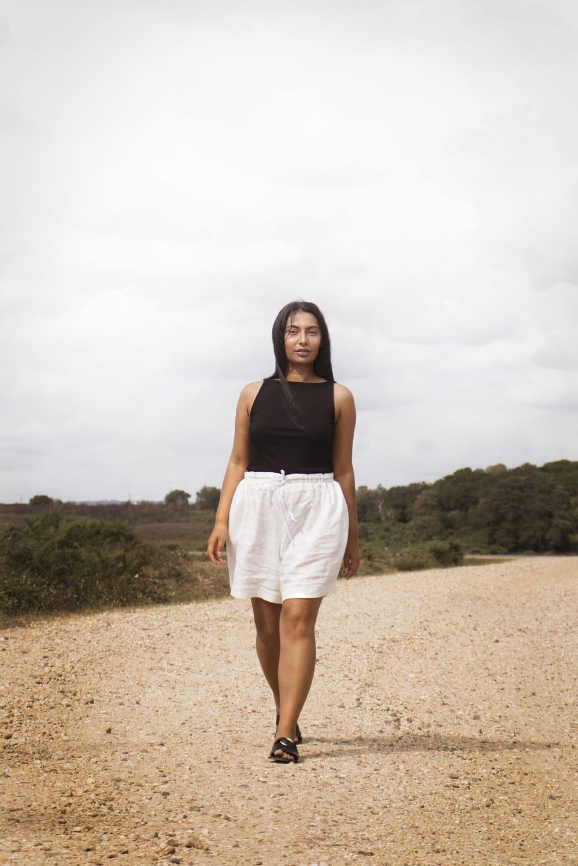 model walking in white linen shorts