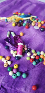 purple fabric with colourful beads