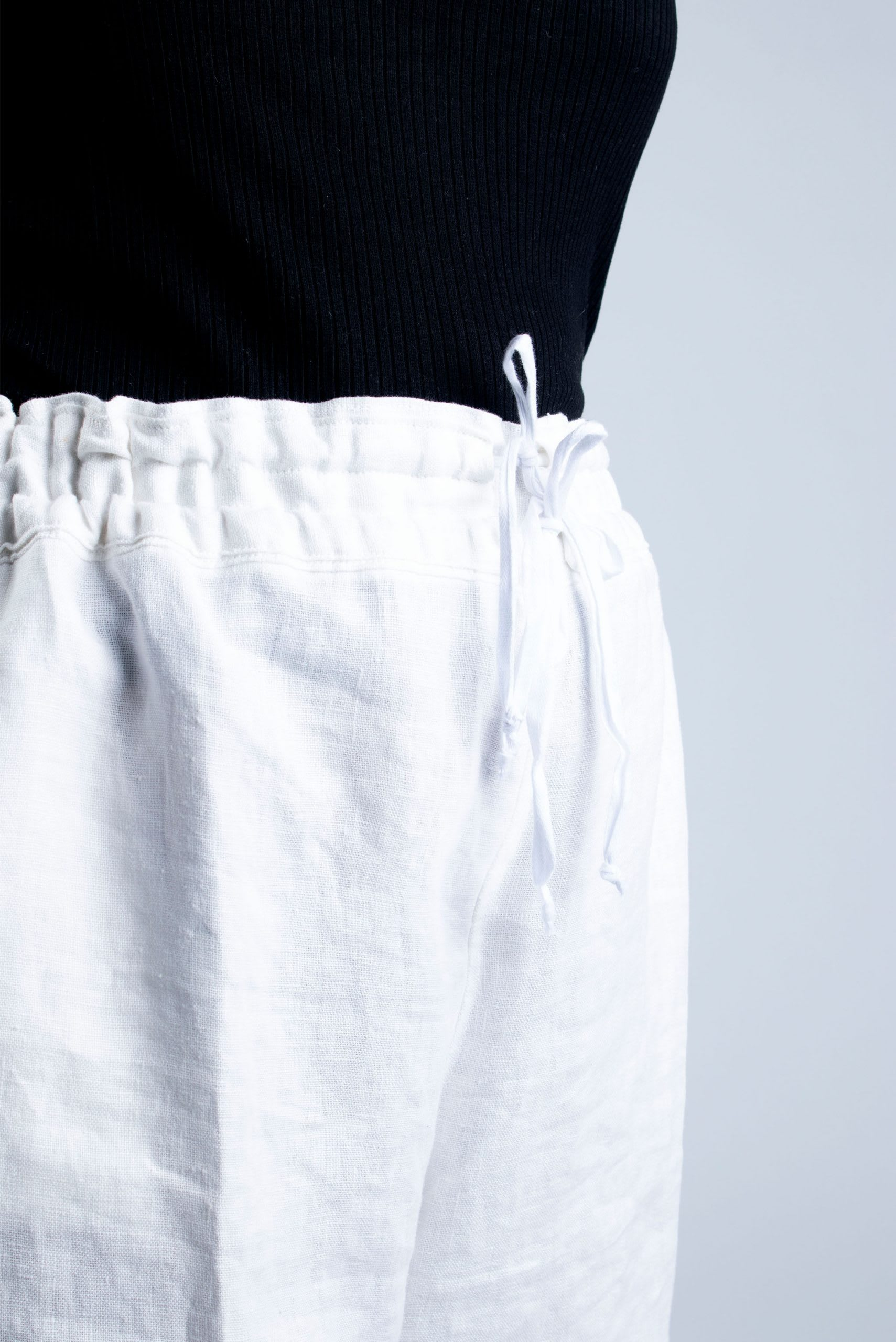 detail of drawstring on white linen shorts
