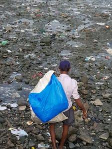 Man searching through sewage and rubbish