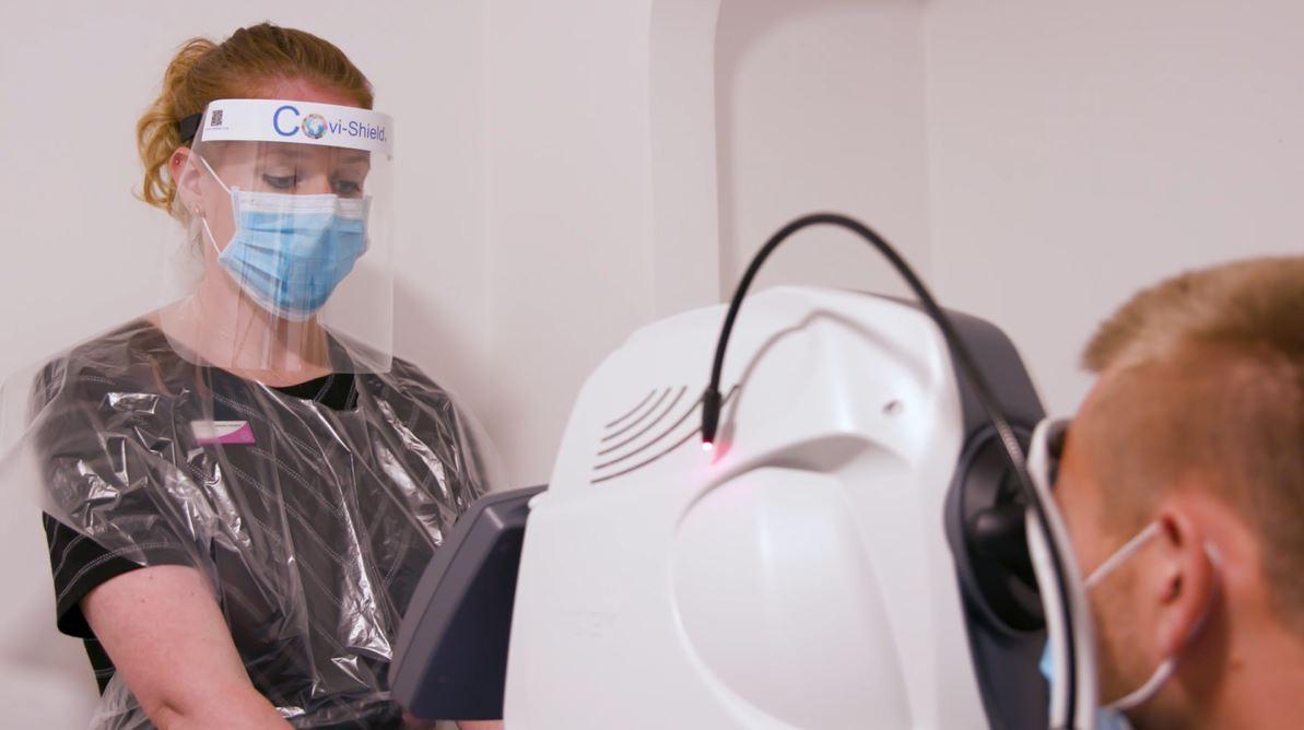 Optometrist wearing a face mask doing an eye test