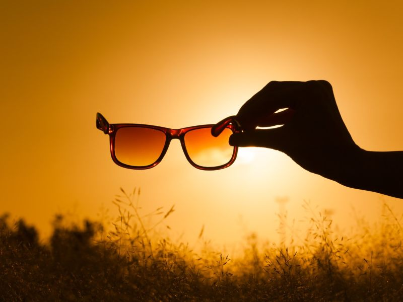 Sunglasses being held up to sunset