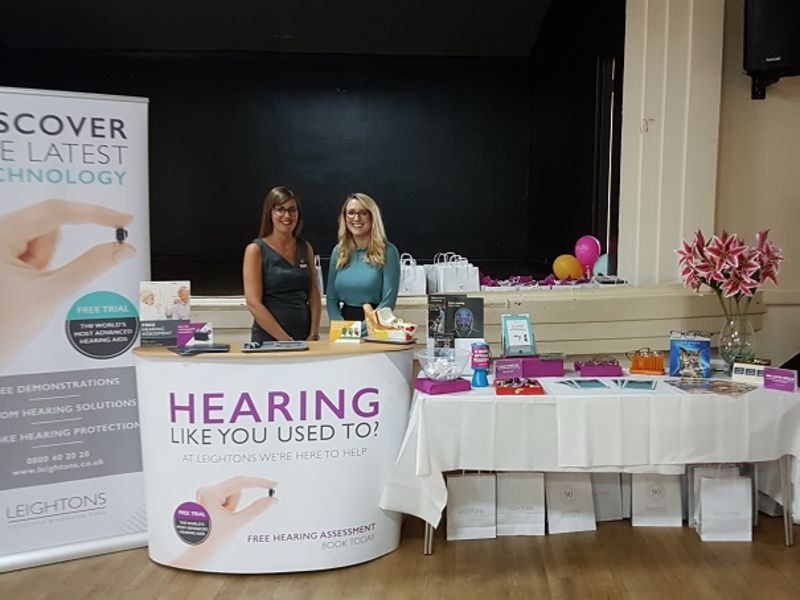 Two women at Open Sight fair stand
