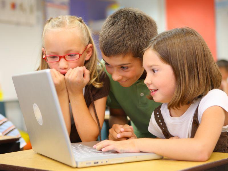 Children gathered round laptop