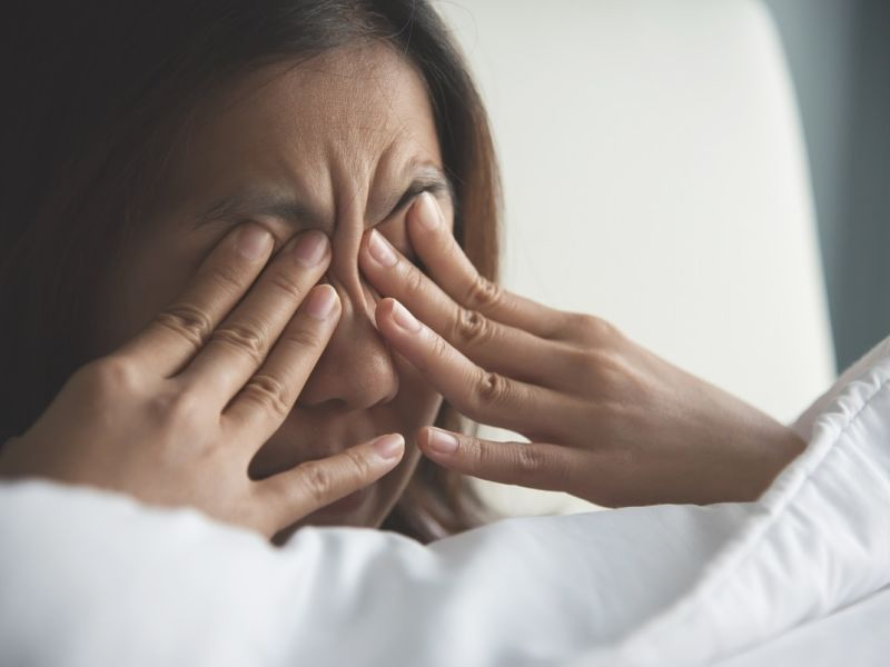 Woman rubbing eyes with fingers