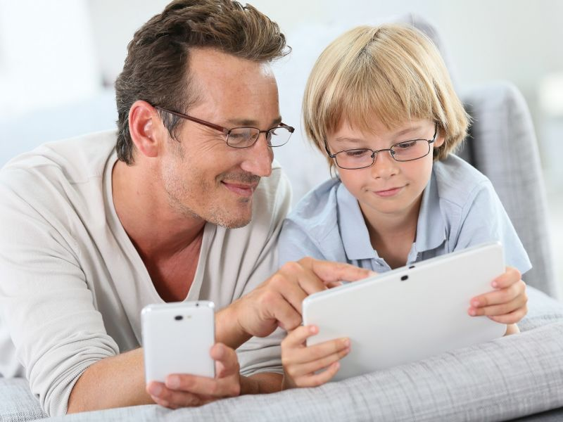 Man and child using phone and tablet