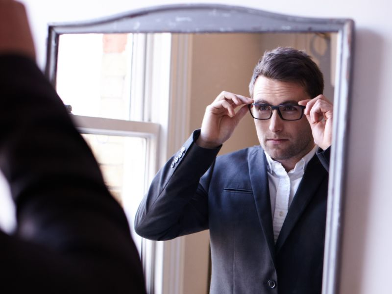Man checking out glasses in mirror