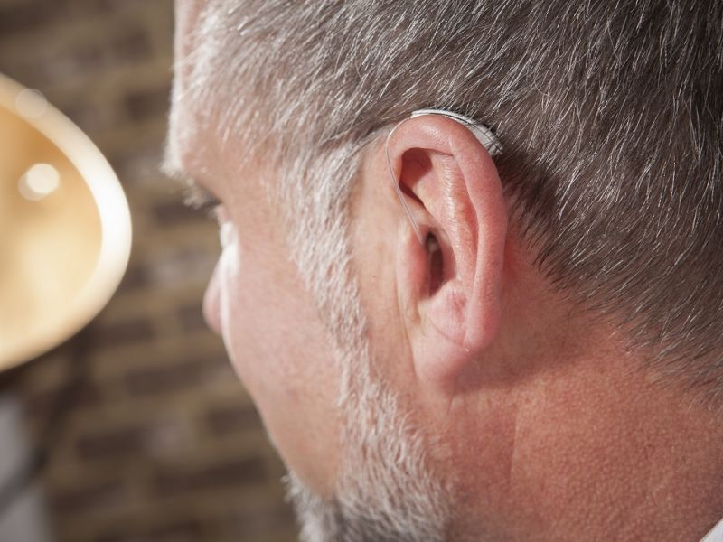 Close up of hearing aid in mans ear