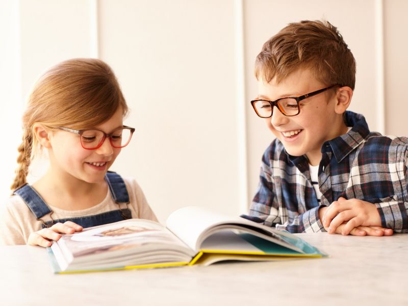 Children wearing glasses and reading book