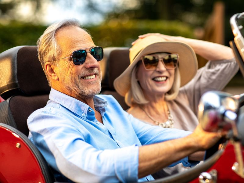 retired couple driving on holiday with sunglasses