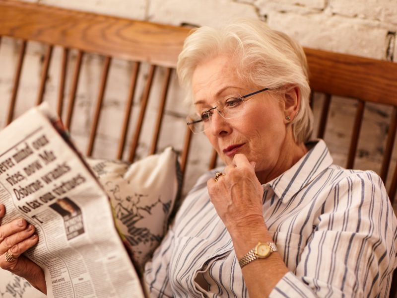 Woman sat down reading newspaper