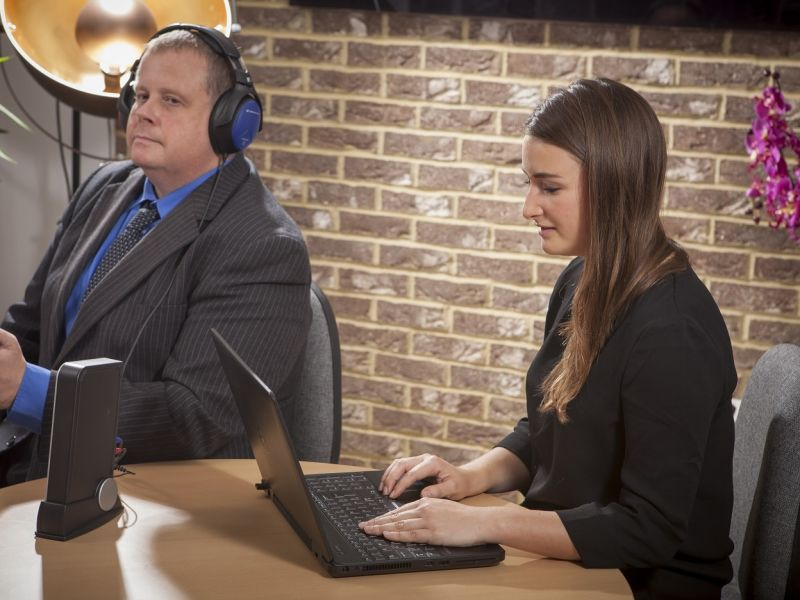 Woman on laptop and man with headphones