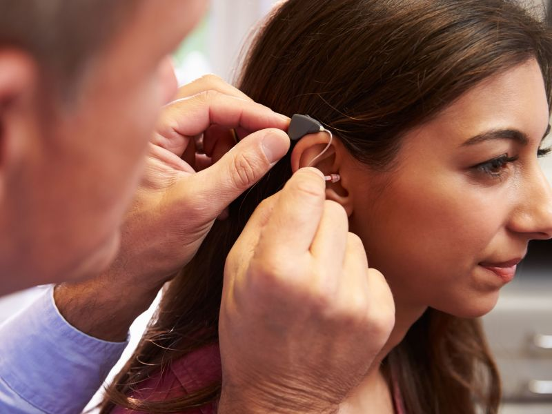 Man placing hearing aid into woman's ear