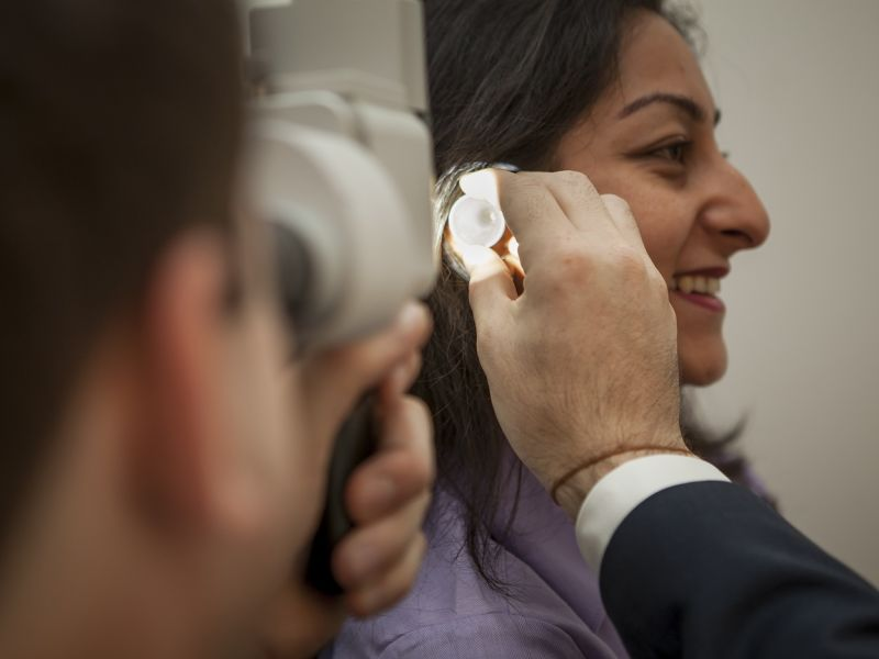 Man inspecting inside of woman's ear