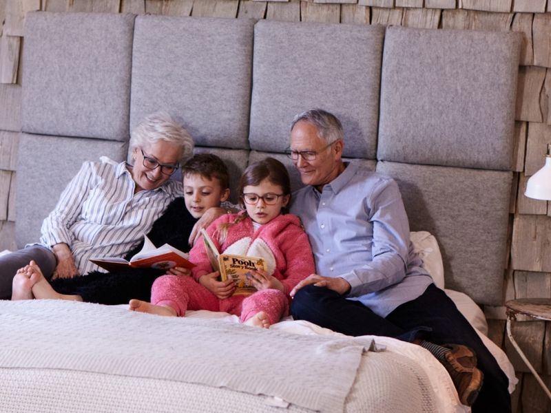 Family in bed reading books
