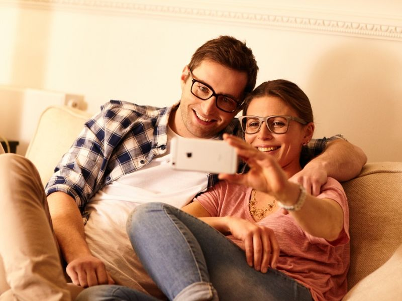 Couple on sofa wearing glasses and taking a selfie