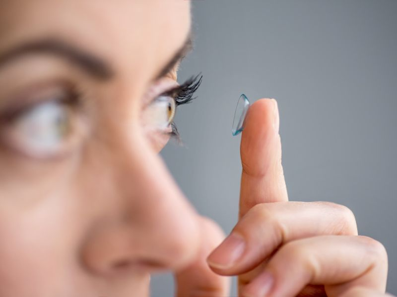 Woman putting contact lense in eye