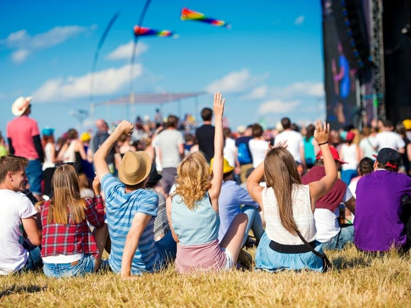 Young people sat facing stage at a festival
