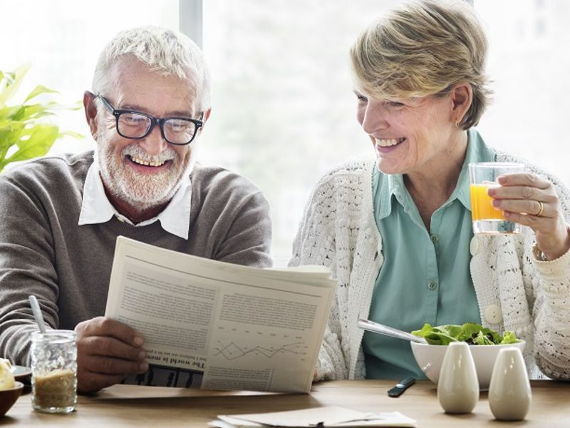 Man and woman smiling reading newspaper