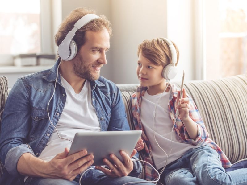 man and son on sofa listening to headphones