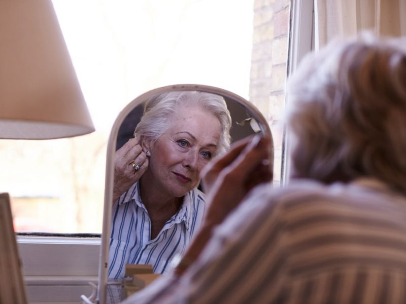 Woman inserting hearing aid looking in mirror