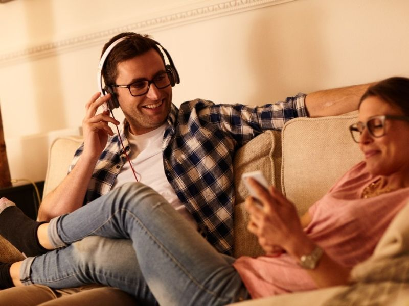 Woman laid down with legs over man in headphones