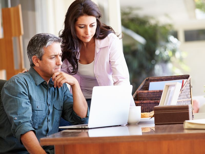 Man and woman looking concerned at laptop