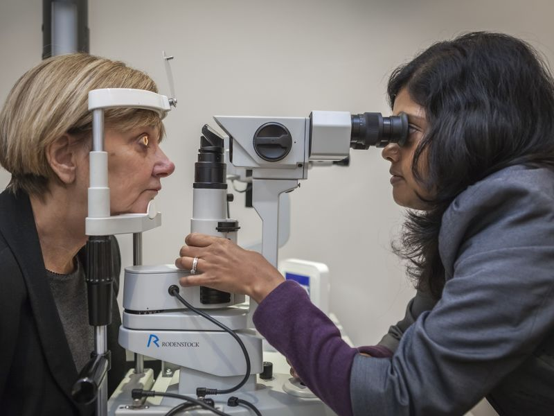 Optometrist performing eye test on woman