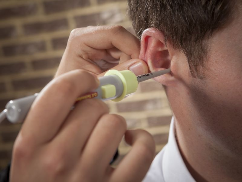 Man probing ear with ear wax cleaner