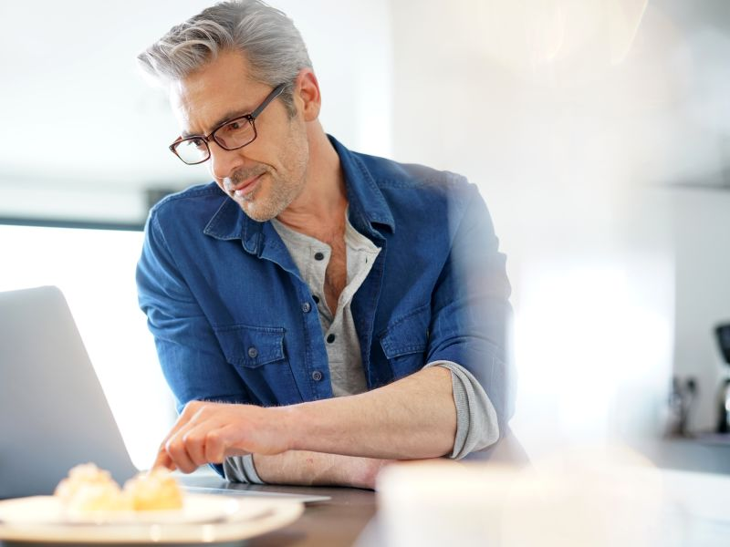Man using laptop wearing glasses
