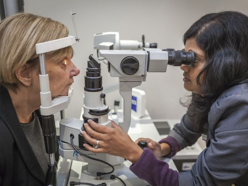 Optometrist performing eye test on woman