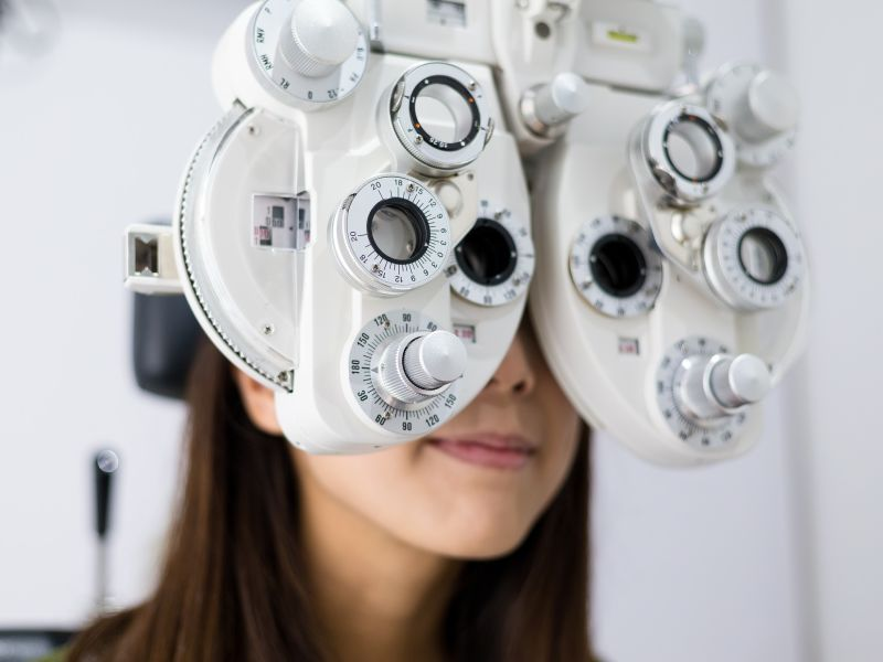 Woman having Leightons eye test with phoropter head technology