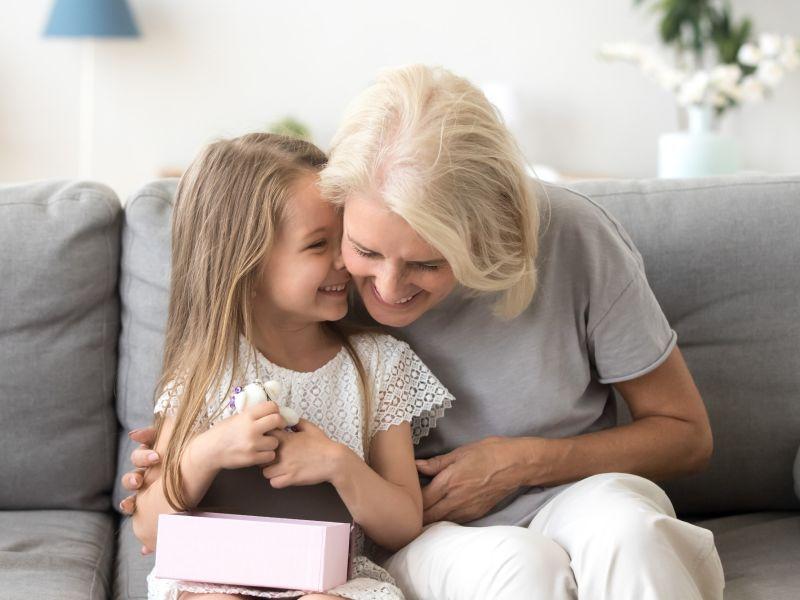 girl whispering to joke to grandmother