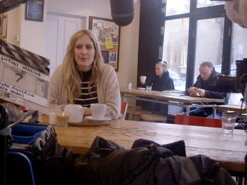 Woman being filmed in a café