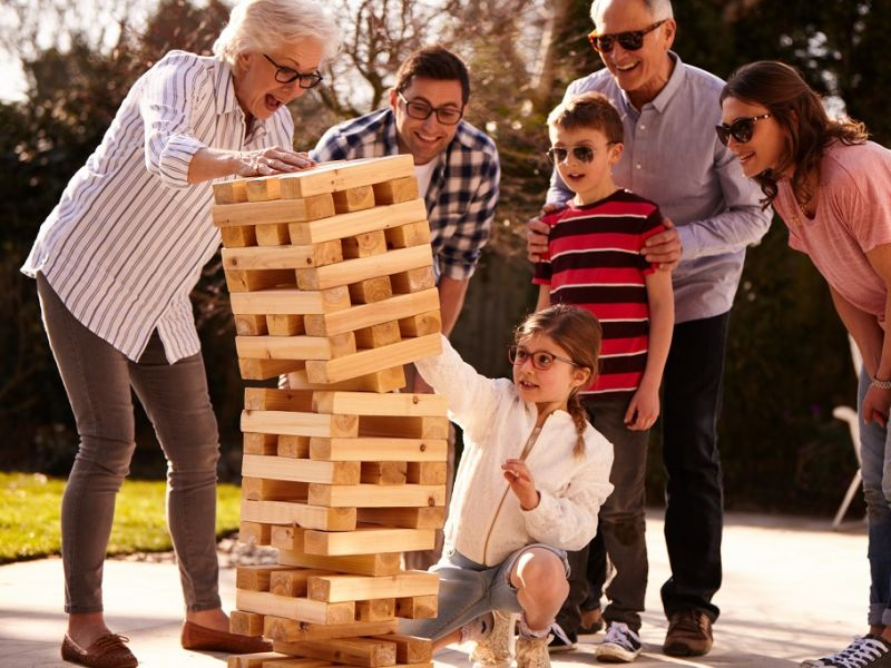 Child knocking over Jenga playing with family
