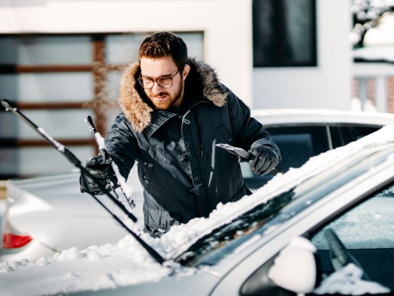 Young man in glasses preparing his car for the snow
