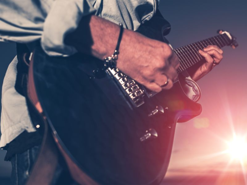 Man playing guitar with sunset backdrop