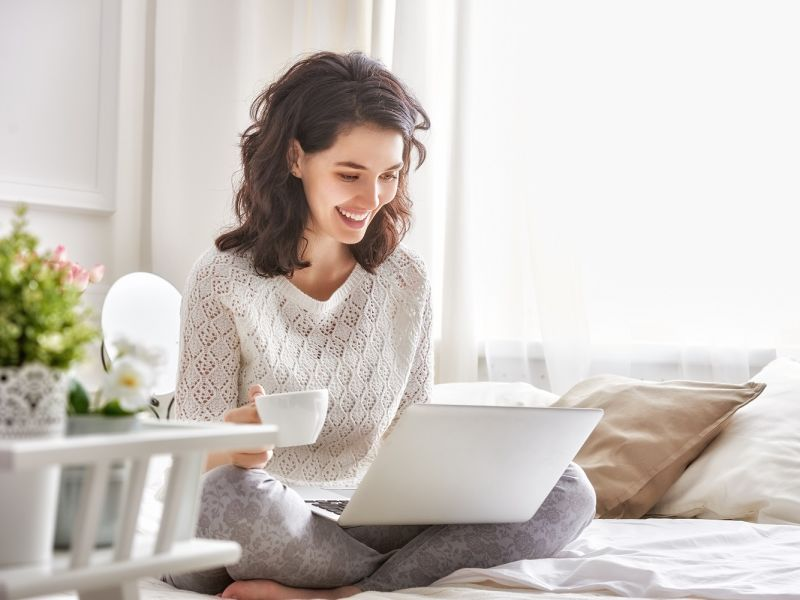 Woman on laptop drinking coffee