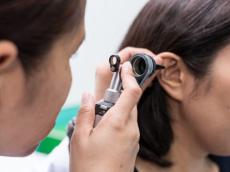 Man inspecting inside of woman's ear