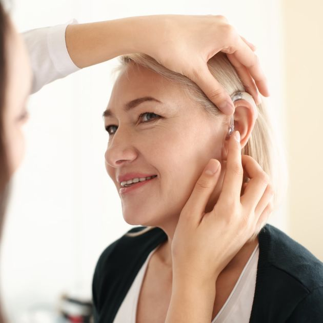 blonde woman having behind the ear hearing aid fitted