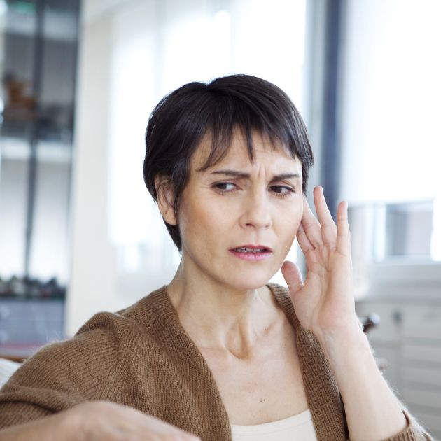 woman holding her ear, concerned about her hearing