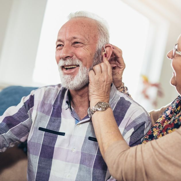 Elderly couple fitting a hearing aid
