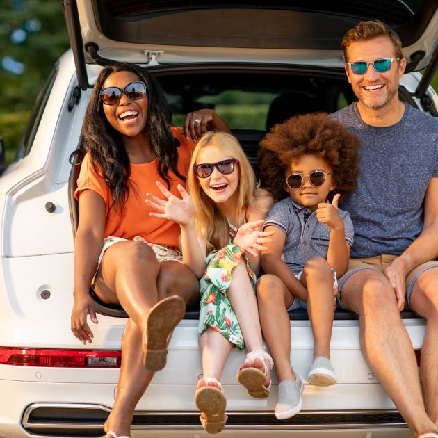 Family of four wearing sunglasses sitting in car boot