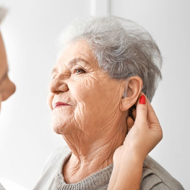 elderly woman having hearing aid fitted