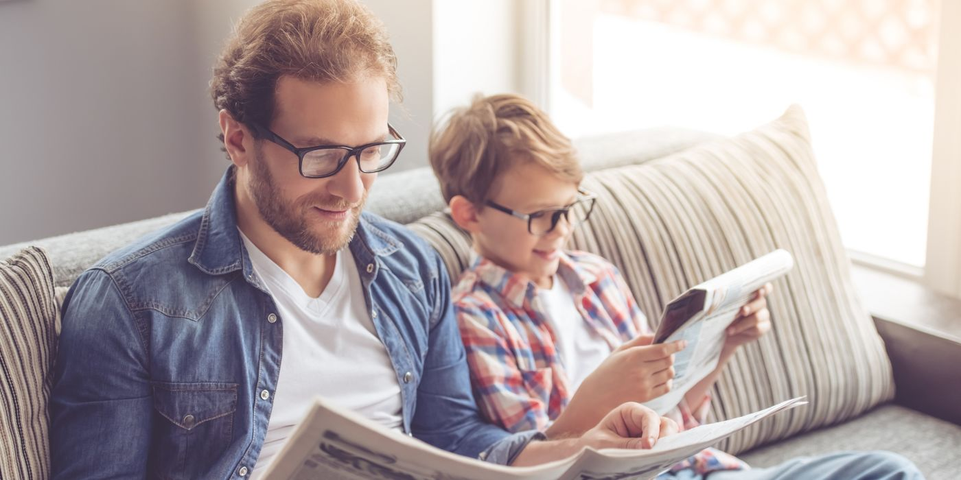 Father and son reading on sofa with glasses on