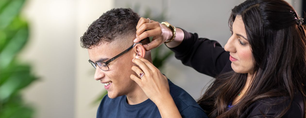 Audiologist Salma fitting a hearing aid
