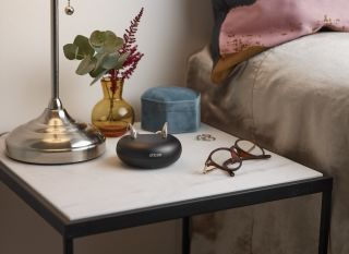 Hearing aids in charging dock beside bed